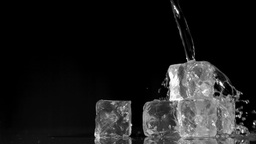 Water being poured in super slow motion onto ice c Stock Video Footage