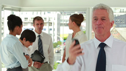 Happy director on the phone with employee in backg Stock Video Footage