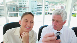 Mature businessman explaining something to a young woman Live Action