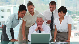 Business team around their boss watching a laptop  Footage