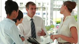 Businessman holding an organizer talking to collea Stock Video Footage