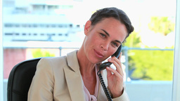 Businesswoman on the phone and looking at camera Footage