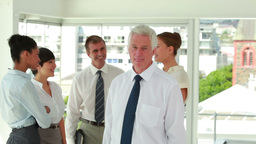 Businessman posing with his team in background Stock Video Footage