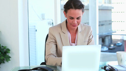 Businesswoman at her desk looking at camera Stock Video Footage