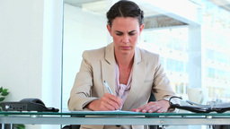 Woman in suit writing while sitting at her desk Stock Video Footage
