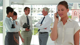 Businesswoman on the phone with colleagues in back Footage