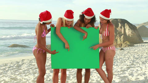 Four girls wearing christmas hats at the beach Footage