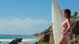 Woman holding her surfboard as she looks at the wa Stock Video Footage