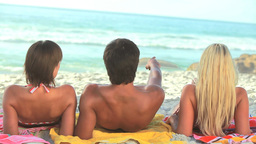 Three friends sit on their towels on the sand Stock Video Footage