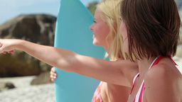 Women standing by the surfboard pointing outwards Footage