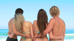 Four friends staring out at the ocean Stock Video Footage