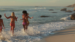 Four women at the beach playing in the water Footage