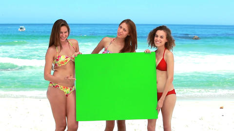 Three girls hold a green screen Stock Video Footage
