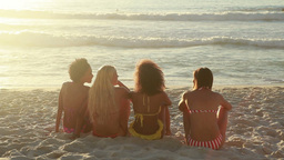 Four girls sit on the beach together Stock Video Footage