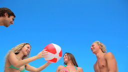Four friends playing with an inflatable beach ball Footage