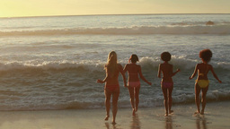 Four female friends run into the water together Footage