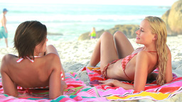 Two women lying down on their beach towels Footage