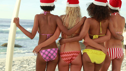 Four women standing while wearing Christmas hats Footage