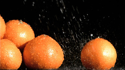 Tasty oranges in super slow motion receiving water Stock Video Footage