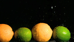 Lemons and limes in super slow motion receiving wa Footage
