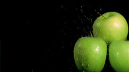 Three apples being watered in super slow motion Footage