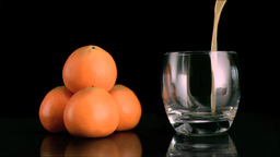 Fresh mandarin juice filling in super slow motion a glass Footage