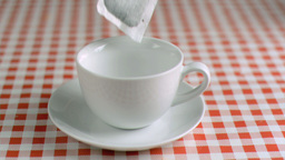 Tea bag falling in super slow motion in a cup Stock Video Footage