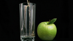 Fresh apple juice flowing in super slow motion in a glass Footage