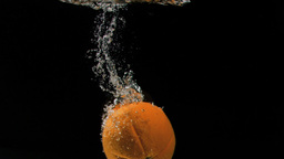 Orange diving in super slow motion into water Footage