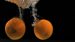 Oranges falling in super slow motion into water Stock Video Footage