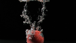 Red apple diving in super slow motion into water Stock Video Footage