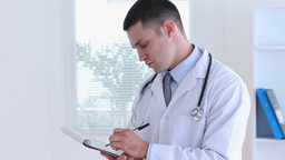 Young doctor writing on a clipboard Footage