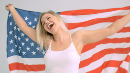 Happy woman in slow motion holding the American fl Footage
