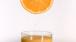 Drops of orange juice in super slow motion falling Footage