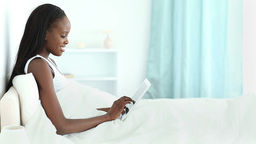 Woman lying in her bed while typing on a tablet ta Footage