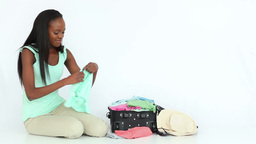 Smiling woman folding clothes while sitting on the Stock Video Footage