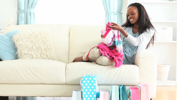 Woman sitting on a couch and looking clothes Footage