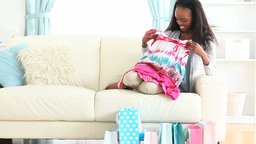 Woman sitting on a couch and looking clothes Stock Video Footage