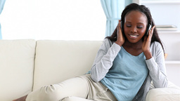 Smiling woman listening to music on a sofa Footage