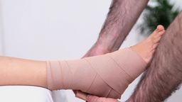 Physiotherapist strapping the ankle of his patient Footage