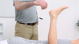 Physiotherapist testing the reflex of the ankle Stock Video Footage