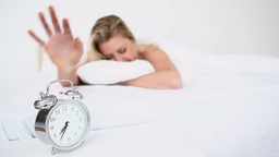Alarm clock ringing while a woman sleeps Footage