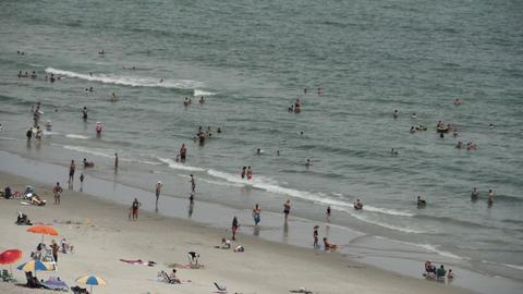 1823 People Enjoying the Beach with Ocean Waves in Stock Video Footage