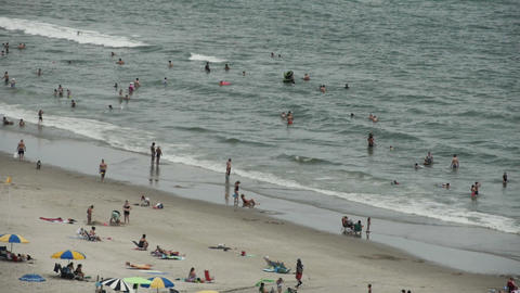 1825 People Enjoying the Beach with Ocean Waves in Stock Video Footage