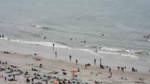 1828 People Enjoying the Beach with Ocean Waves in Footage