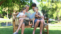 Family sitting on a bench reading a book Footage