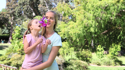 Mother and his daughter blowing on a pinwheel Footage