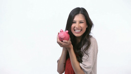 Happy woman kissing a piggy bank Footage