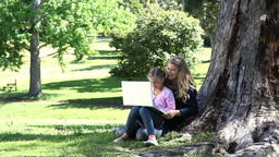 Mother and her daughter reading a book in a park Footage
