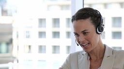 Business woman laughing while talking into a heads Footage